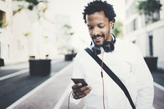 Young bearded African man looking at smartphone in hands while walking at sunny city street.Concept of happy business Stock Photo