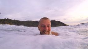 Young bearded athletic man making selfie in the sea and diving under water. Gopro HD slow motion. Phuket, Thailand. stock footage