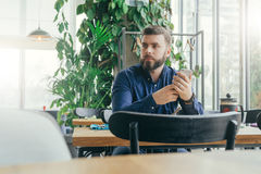 Young bearded attractive businessman in blue shirt is sitting at wooden table near window in restaurant Stock Photo