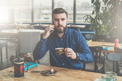 Young bearded attractive businessman in blue shirt is sitting at wooden table in restaurant, talking on phone Stock Image