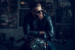 Young Biker in Sunglasses on Motorcycle in Garage. Young Bearded Biker Sitting on Motorcycle in Garage. Indoor Garage. Young Mechanic in Garage. Parts of royalty free stock image