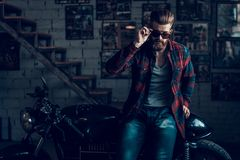 Young Biker in Sunglasses on Motorcycle in Garage. Young Bearded Biker in Sunglasses Sitting on Motorcycle in Garage. Indoor Garage. Young Mechanic in Garage stock image
