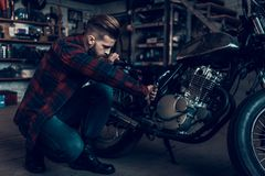 Young Bearded Biker Tuning Motorcycle in Garage. Indoor Garage. Young Mechanic in Garage. Parts of Motorcycle. Man in Checkered Shirt. Man and Vintage Bike royalty free stock images