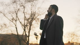 Young bearded business man in coat talking at smartphone and making deals on street with sunlight backlit in evening stock footage