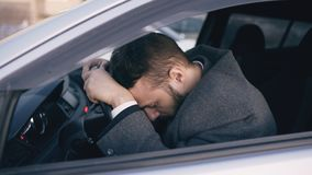 Young bearded business man sitting in car very upset and stressed after hard failure and moving in traffic jam. Young bearded business man sitting in car very Royalty Free Stock Photography