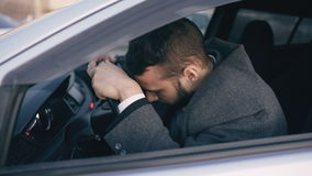 Young bearded business man sitting in car very upset and stressed after hard failure and moving in traffic jam. Young bearded business man sitting in car very stock video footage
