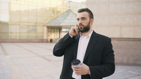 Young bearded business man talking at smartphone with cup of coffee near modern office buildings stock footage