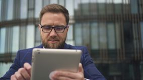 Young bearded business owner is using tablet, smiling on office building background. stock video footage