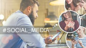 Young bearded businessman in blue shirt sits at table in cafe and use smartphone, laptop in front of him. Stock Photos