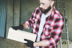 Young bearded businessman, builder, repairman, carpenter, architect, designer dressed in plaid shirt, glasses and gloves. Stands in workshop, holds a wooden Stock Image