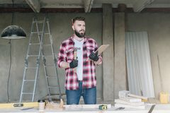Young bearded businessman,builder,repairman,carpenter,architect, designer, on table construction tools. stock image