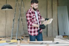 Young bearded businessman,builder,repairman,carpenter,architect, designer, handyman dressed in plaid shirt, goggles. And gloves, stands in workshop and measures Stock Photography