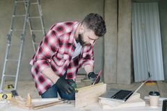 Young bearded businessman, builder, repairman, carpenter, architect, designer, handyman dressed in plaid shirt. Goggles and gloves, stands in workshop in front Royalty Free Stock Photo