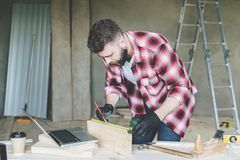 Young bearded businessman, builder, repairman, carpenter, architect, designer, handyman dressed in plaid shirt, goggles. And gloves, stands in workshop in front royalty free stock photos