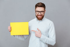 Young bearded businessman holding copyspace blank. Picture of cheerful young bearded businessman holding copyspace blank and pointing standing over grey Stock Photography