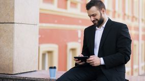 Young bearded businessman reading news on tablet computer and drink coffee during break near his office building Stock Photos