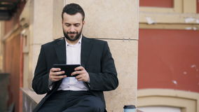 Young bearded businessman reading news on tablet computer and drink coffee during break near his office building stock footage