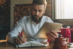 Young bearded businessman sits in cafe, home at table, holding tablet computer and writes in notebook. Royalty Free Stock Photos
