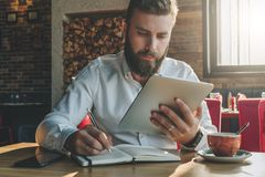 Young bearded businessman sits in cafe, home at table, looking at screen of tablet computer and writes in notebook. Royalty Free Stock Photography