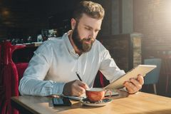 Young bearded businessman sits in cafe, home at table, uses tablet computer and writes in notebook. Royalty Free Stock Photo