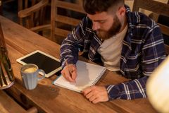 Young bearded businessman sits in cafe, home at table and writes in notebook, near lies tablet computer with black. Screen. Man is working, studying. Online Royalty Free Stock Photography