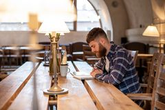 Young bearded businessman sits in cafe, home at table and writes in notebook, near lies tablet computer. Man is working. Studying. Online education, marketing Royalty Free Stock Photos