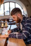 Young bearded businessman sits in cafe, home at table and writes in notebook, near lies tablet computer. Man is working. Studying. Online education, marketing Stock Photos