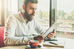 Young bearded businessman sits in cafe at table, holding tablet computer, working.On table cup of coffee, notebook Royalty Free Stock Image