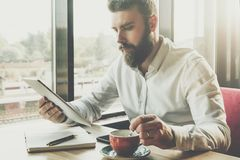 Young bearded businessman sits in cafe at table, uses digital tablet.On desk is notebook,cup of coffee.Man working Royalty Free Stock Image