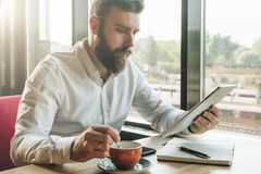 Young bearded businessman sits in cafe at table, uses digital tablet, drinks coffee.On desk is notebook, smartphone. Stock Image