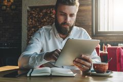 Young bearded businessman sits in office at table,uses tablet computer. On desk is notebook,smartphone, cup of tea. Stock Photo