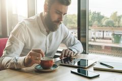 Young bearded businessman sits in office at table,uses tablet computer, drinks coffee.On desk is notebook,smartphone. Royalty Free Stock Images