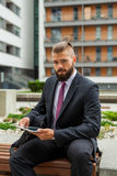 Young bearded businessman sitting on a bench and using tablet pc Stock Images