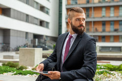 Young bearded businessman sitting on a bench and using tablet pc Royalty Free Stock Photography