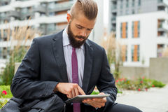 Young bearded businessman sitting on a bench and using tablet pc. Outdoor photo Royalty Free Stock Photos