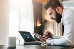 Young bearded businessman sitting at desk in front of laptop with an inscription e-learning on screen. Making notes in tablet computer. Freelancer works Royalty Free Stock Photography