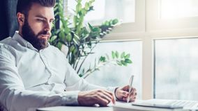 Young bearded businessman is sitting at table in office in front of laptop near window and writing in notebook. Man takes notes in a notepad. Distance work Royalty Free Stock Photography