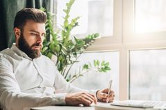 Young bearded businessman is sitting at table in office in front of laptop near window and writing in notebook. Man takes notes in a notepad. Distance work Royalty Free Stock Images