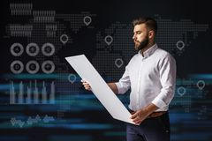 Young bearded businessman standing and holding tablet. Virtual world map with icons of points, graphics, diagrams. Young bearded businessman, dressed in white Royalty Free Stock Photo