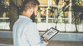 Young bearded businessman standing in office, using tablet computer with graphs, diagrams and charts on screen. Rear view. Young bearded businessman standing in Stock Photography