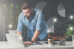Young bearded businessman stands in office near table and uses laptop.On table is tablet computer, smartphone. Royalty Free Stock Photo