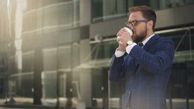Young bearded businessman talking on phone, drinking coffee standing on city street. stock footage