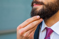 Young bearded businessman thinking abut plans for the weekend. Royalty Free Stock Images
