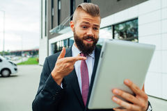 Young bearded businessman using his tablet pc. He is surprised. Stock Images
