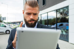 Young bearded businessman using his tablet pc. He is surprised. Stock Photography