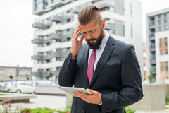Young bearded businessman using his tablet pc. He is surprised. Royalty Free Stock Images