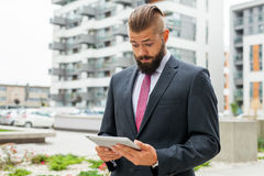 Young bearded businessman using his tablet pc. He is surprised. Stock Image