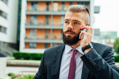 Young bearded businessman using mobile phone outside the office. Stock Photography