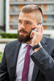 Young bearded businessman using mobile phone outside the office. Royalty Free Stock Photo