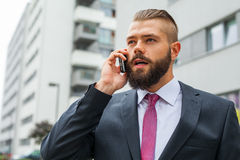 Young bearded businessman using mobile phone outside the office. Royalty Free Stock Images
